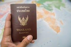 Рука ` s человека держа пасспорт Таиланда Предпосылка карты готовый перемещать Стоковая Фотография