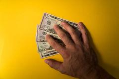 Рука ` s человека покрыла банкноты долларов защищать дег ваш Нехватка денег Доллары крупного плана банкнот Стоковая Фотография