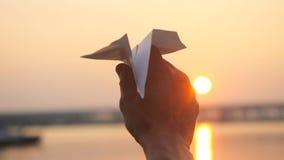 Рука ` s человека самолета бумаги старта против моря во время захода солнца с пирофакелом солнца и отражений в воде в slowmotion Стоковые Фотографии RF