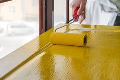 Рука ` s человека с роликом красит деревянную дверь в ярком желтом цвете Стоковая Фотография