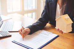 Руки агента недвижимости указывают к договору подряда в офисе имущественного агентства недвижимости стоковое изображение