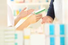 Руки аптекаря продавая медицину к клиенту Стоковая Фотография RF