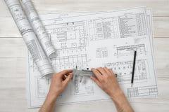 Руки архитектора держа прибор сантиметра над планом чертежа в взгляд сверху Стоковая Фотография RF