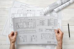 Руки архитектора держа эскиз чертежа Стоковые Фото