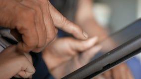 Руки бабушки и ребенка используя таблетку выбирают малую глубину фокуса поля сток-видео