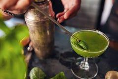 Руки бармена гарнируя свежий зеленый коктеиль Стоковые Изображения