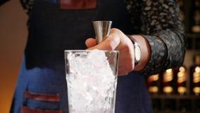Руки бармена лить ингредиент коктейля в измеряя чашке или джиггере сток-видео
