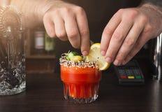 Руки бармена подготавливая коктеиль на счетчике бара стоковая фотография