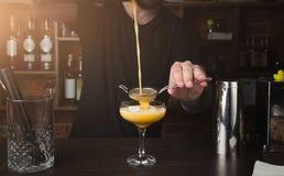 Руки бармена подготавливая коктеиль на счетчике бара Стоковое Фото