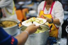 Руки бедных приносят контейнер для того чтобы заполнить еду для того чтобы принести назад к размещещнию стоковая фотография