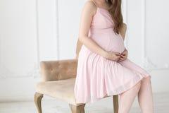 Руки беременной женщины на животе Стоковое Изображение