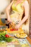 Руки беременной женщины s и вырезывание живота на кухне с здоровой едой Стоковая Фотография RF