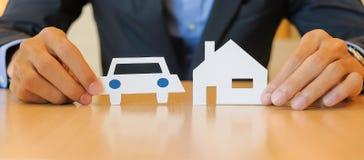 Руки бизнесмена держа автомобиль и бумагу дома стоковые изображения