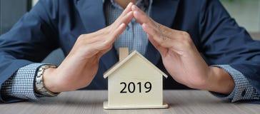 Руки бизнесмена держа деревянную модель дома Страхование собственности и недвижимость стоковые изображения