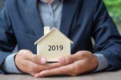 Руки бизнесмена держа деревянную модель дома Страхование собственности и недвижимость стоковые изображения rf