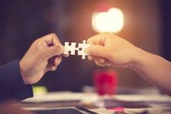 2 руки бизнесмена для того чтобы соединить часть головоломки пар с предпосылкой неба Зигзага головоломка самостоятельно деревянна стоковое изображение