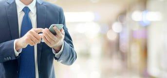 Руки бизнесмена используя умный телефон над офисом нерезкости с экземпляром Стоковые Фото