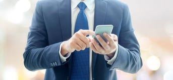 Руки бизнесмена используя умный телефон над офисом нерезкости с экземпляром Стоковое Фото