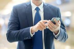 Руки бизнесмена используя умный телефон над офисом нерезкости с bokeh Стоковые Изображения RF