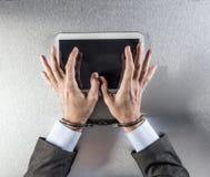 Руки бизнесмена используя цифровую таблетку с невольничьими наручниками Стоковое Фото