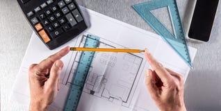 Руки бизнесмена или архитектора в отражении на свойстве, над взглядом Стоковые Изображения