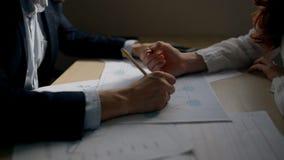 Руки бизнесмена и коммерсантки работая на финансовой диаграмме в офисе видеоматериал