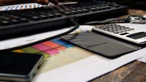 Руки бизнесмена печатая на клавиатуре и подписывают документ Стоковая Фотография