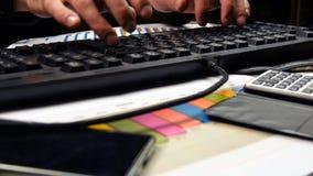 Руки бизнесмена печатая на клавиатуре и подписывают документ Стоковые Изображения RF