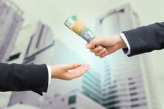 Руки бизнесмена проходя австралийский доллар & x28; AUD& x29; банкнота Стоковая Фотография RF