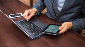 Руки бизнесмена с компьтер-книжкой, мобильным телефоном и таблеткой. Стоковое Изображение