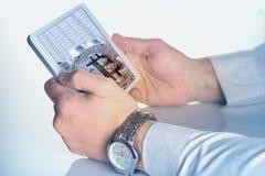 Руки бизнесмена с таблеткой и bitcoin с таблицей на s Стоковое Изображение