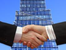 руки бизнесменов передние трястия небоскреб Стоковая Фотография RF