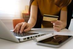 Руки бизнес-леди используя smartphone и кредитную карточку держать с цифровым слоем стоковая фотография