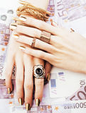 Руки богатой женщины с золотым маникюром и много колец ювелирных изделий Стоковая Фотография
