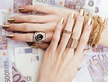 Руки богатой женщины с золотым маникюром и много Стоковые Изображения RF