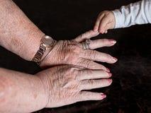 Руки большей бабушки и ее большего внука младенца стоковое изображение