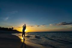 Руки вверх по женщине представляя на пляже с красивым небом захода солнца, предпосылкой облаков r Йога Кубы Варадеро стоковое изображение