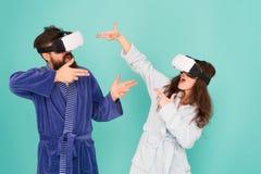 Руки вверх Стойте и поставляйте Технология и будущее VR Возбуждая впечатления Пары в купальных халатах носят стекла VR Игра стоковое фото