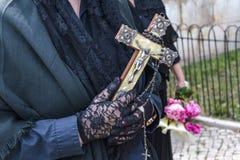 Руки вдовы держа религиозный крест и розарий стоковая фотография rf