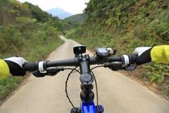 Руки велосипедиста ехать горный велосипед на следе леса Стоковое Фото