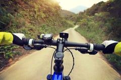 Руки велосипедиста ехать горный велосипед на следе леса Стоковое Изображение