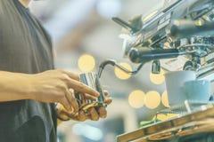 Руки взгляда конца-вверх профессионального barista работая в кофейне подготавливая кофе эспрессо, на машине кофе Стоковое фото RF
