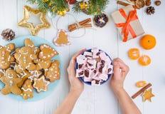 Руки взгляд сверху женские держа чашку горячего какао с murshmellows на деревянном столе с подарочной коробкой, gingerbred печень Стоковое Изображение RF