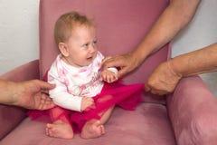 Плача малыш Руки взрослых, родители пробуя утихомирить вниз плача малыша стоковые изображения