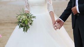 Руки владением жениха и невеста Невеста имеет букет в ее руках сток-видео