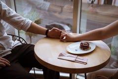 Руки владением мальчика и девушки в кафе стоковые изображения