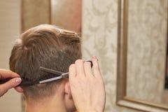 Руки волос вырезывания парикмахера Стоковое фото RF