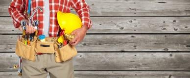 Руки водопроводчика с шлемом и водопроводным краном стоковая фотография