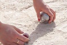 Руки выбирая вверх шарик игры в петанки и jack Стоковые Изображения