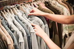 Руки выбирая одежды на шкафе в выставочном зале Стоковая Фотография RF
